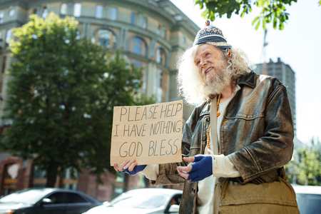 Long-haired homeless. Long-haired homeless man feeling a little bit hopeless while standing near traffic asking for help Фото со стока