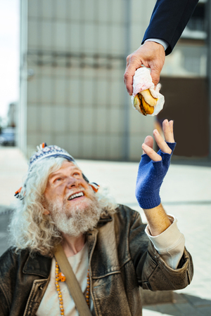 That burger. Homeless man wearing old leather jacket taking burger from kind stranger aiming for helping him Stock fotó