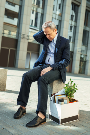 Personnel redundancy. Elderly wrinkled man feeling unbelievably sad after personnel redundancy at his work place Stock Photo