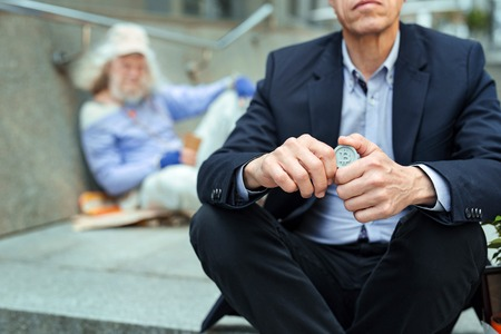 Coin for man. Helpful supportive office manager feeling friendly while holding coin for homeless man Stock Photo