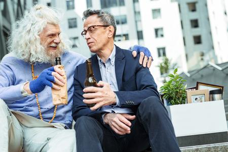 Depressed man. Just fired depressed man wearing glasses drinking beer while having big emotional stress