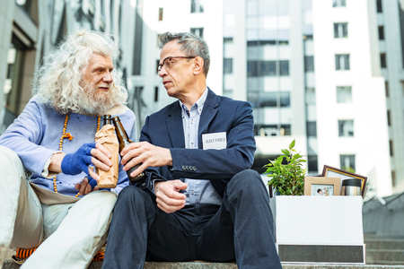 Beer bottles. Two unemployed stressed men clanging their beer bottles while drinking alcohol sitting outside office building Stock Photo