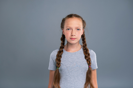 Tender beauty. The portrait of a charming teenage girl with two braids posing for the camera while standing isolated on a blue-grey background