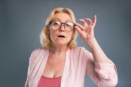 Haughty attitude. Pretty senior woman adjusting her eyeglasses and casting a haughty look while standing isolated on a blue-grey background Stock Photo