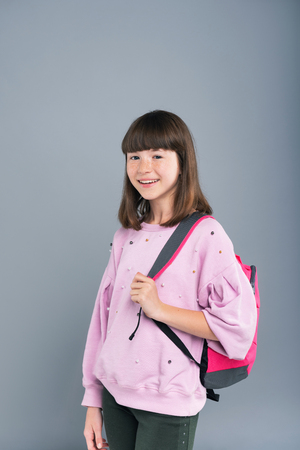 Ready for school. Cheerful teenage girl wearing a backpack on her shoulder and smiling at the camera while posing isolated on a blue-grey background