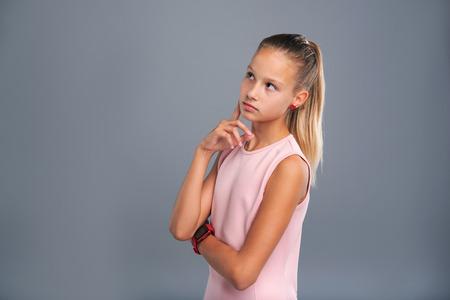 Fresh ideas. Petite teenage girl in a pink top touching her cheek with a finger while contemplating something and considering new ideas 版權商用圖片