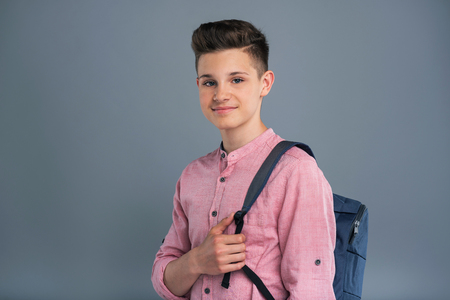 Ready to study. Joyful teenage boy wearing a blue backpack and posing for the camera while standing isolated on a blue-grey background 免版税图像