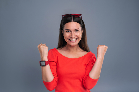 Awesome achievement. Upbeat young woman in a red dress grinning and doing fist pumps while posing isolated on a blue-grey background