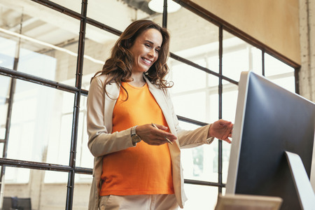 Working process. Low angle of optimistic pregnant CEO standing and laughing