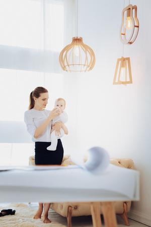 Modern room. Delighted woman spending break with her kid, standing near sofa