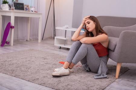 Mi manca. Ragazza teenager triste che tocca la testa e che si siede sul pavimento