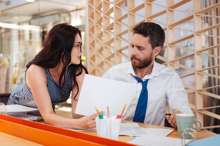 Great desire. Inspired dark-haired woman seducing her boss while standing at his table Stock Photo