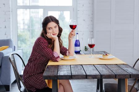 Striped dress. Stylish elegant woman wearing nice striped dress drinking wine alone after breakup with boyfriend