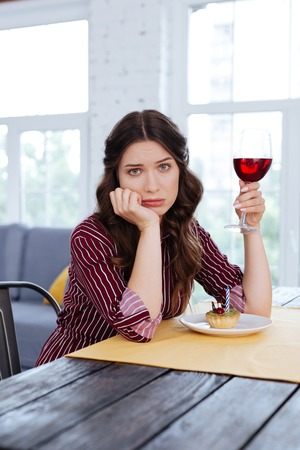 Waiting for man. Charming elegant woman feeling extremely lonely waiting for her man in restaurant