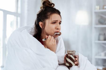 Viendo melodrama. Mujer que se siente emocional mientras ve el melodrama y come chocolate con cuchara