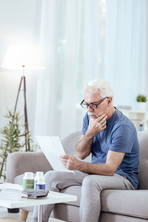 How to use. Reflective senior man wearing glasses and scrutinizing instruction