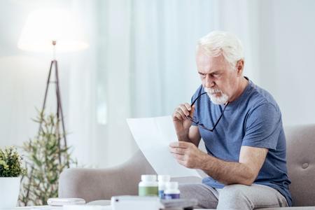 Medication prescription. Musing senior man holding glasses and reading instruction