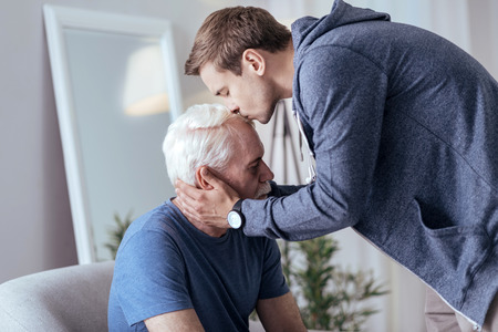 Sincere support. Sincere man kissing senior man and standing Imagens