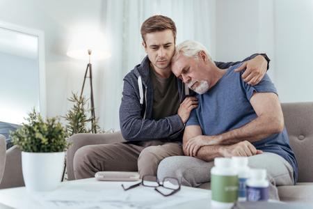 Little rest. Uneasy man hugging senior man who taking nap