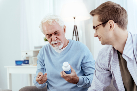 Benefits from drugs. Positive senior man holding pills and talking to man