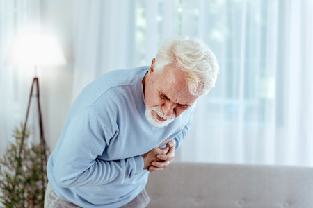Coronary artery disease. Sick senior man touching chest and posing on light background