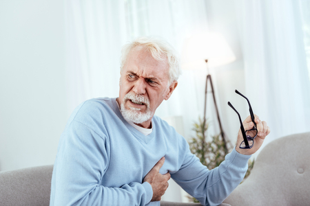 Heart rhythm disturbances. Painful senior man touching chest and holding glasses