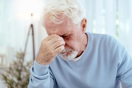 Horrible migraine. Sad senior man touching nose bridge and closing eyes Stock Photo