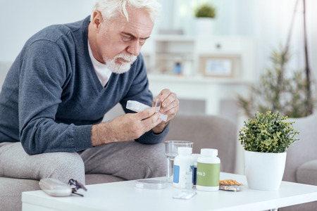 Morning with pills. Pleasant senior man sitting on sofa and getting pills