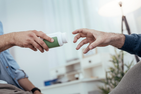 Saving medication. Close up of tensed male hand stretching for bottle filled with pills Stock Photo