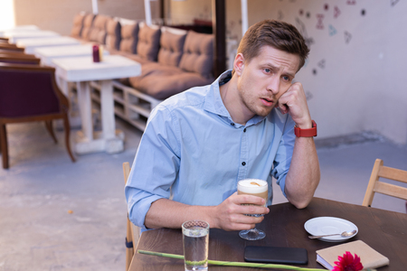 Bored man. Handsome blue-eyed man feeling very bored during his coffee break while sitting alone on summer terrace 스톡 콘텐츠