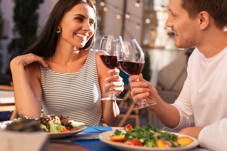Nice earrings. Stylish woman wearing nice earrings drinking wine with her boyfriend