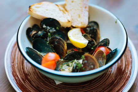 Some mussels. Selective focus of delicious nice mussels with some lemon slices and cherry tomatoes
