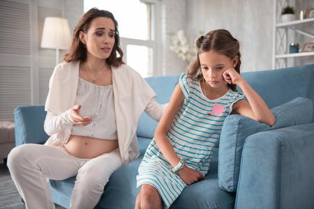 Keine Stimmung. Dunkelhaariges kleines Mädchen im weißen und blauen Kleid, das keine Stimmung hat und mit ihrer schwangeren Mutter spricht Standard-Bild