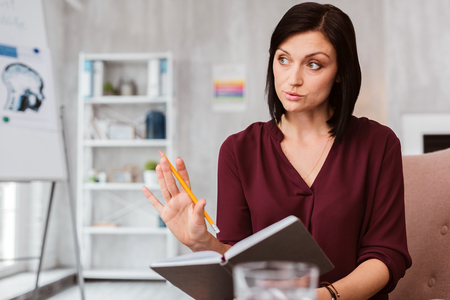 Calm serious doctor putting her hand up and asking the patient to talk about his problem slowly Stock Photo