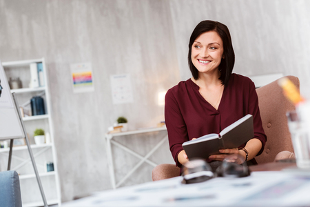 Emotional cheerful psychologist sitting with a notebook in her hands and smiling