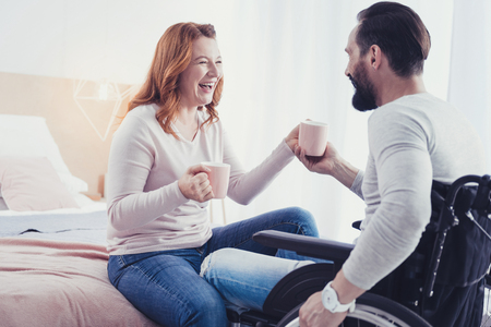 Funny joke. Positive optimistic disabled man drinking tea and looking at his emotional girlfriend laughing at his funny joke