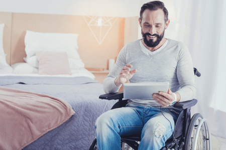 Communicating online. Cheerful friendly young man sitting in a wheelchair and feeling happy while having a pleasant video call