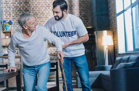 Handsome content dark-eyed man smiling and helping an old man while he standing up