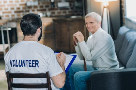Well-built dark-haired volunteer talking with an aged man and conducting a poll while sitting on the chair and the old man smiling Banque d'images