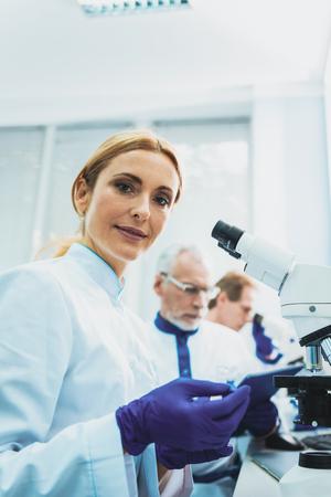 Pretty practitioner sitting in semi position while doing scientific research Foto de archivo