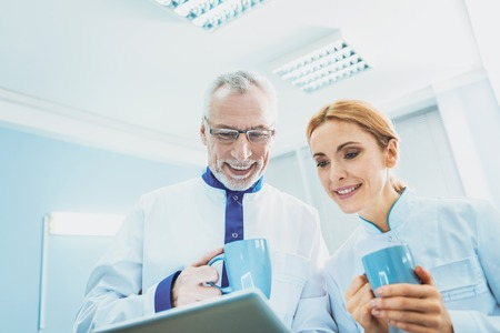 Positive delighted man keeping smile on face while drinking tea with colleague