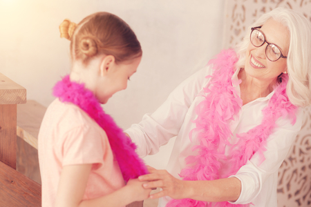 You are so cute. Selective focus on a beautiful retired lady smiling broadly while looking at her adorable granddaughter wearing a feather boa while both having fun at home. Stock Photo