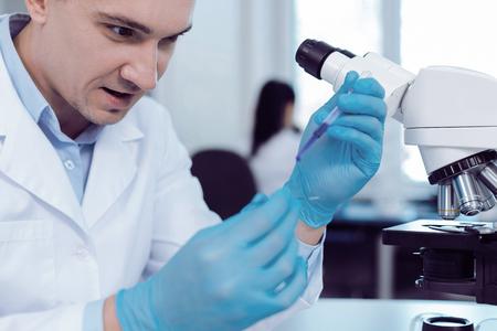 Coinvolto nella ricerca. Intelligente scienziato entusiasta piacevole che indossa guanti di gomma e fa una ricerca biologica mentre indossa guanti di gomma