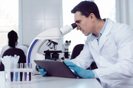 In the lab. Positive smart male scientist holding a tablet and looking into the microscope while working in the biological lab