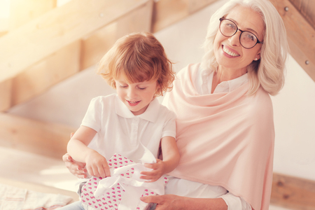 Positive minded elderly lady beaming into the camera while her adorable grandchild sitting on her lap and opening a beautifully wrapped present at home.