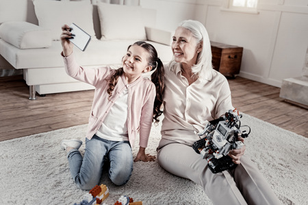 Merry adorable little grandchild and grandmother creating memory holding robot while sitting in the living room