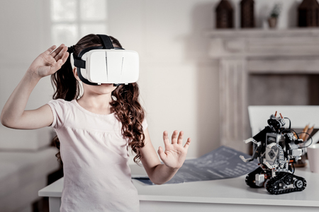 I can touch it. Stricken wave hair small girl in VR glasses moving hands looking straight while robot standing next to her Фото со стока