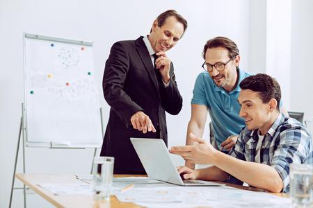 Gute Ergebnisse. Freundlich lächelnde Männer, die stolz auf ihren erfahrenen talentierten Kollegen sind, während sie seine Ergebnisse betrachten