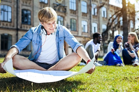 This looks so cool. Smart male student smiling cheerfully while sitting on grass and looking at his technical drawing alone.