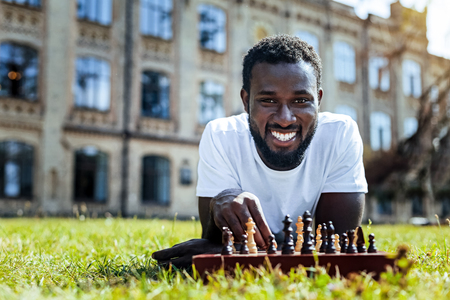 Joyful African American guy looking into the camera and grinning broadly while playing chess on grass.